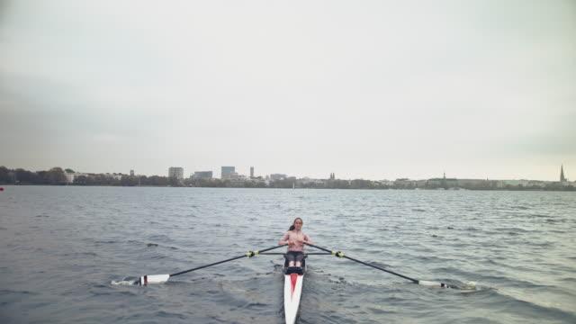 frau rudert ruderboot in fluss gegen himmel - ruderboot stock-videos und b-roll-filmmaterial