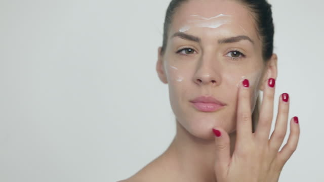 woman rubbing facial mask onto her face - rubbing stock videos and b-roll footage