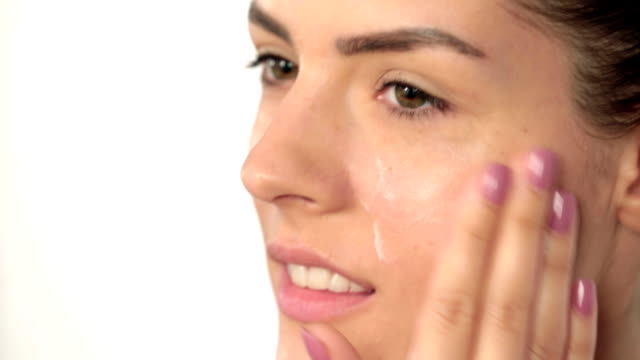 Woman rubbing moisturizer onto face