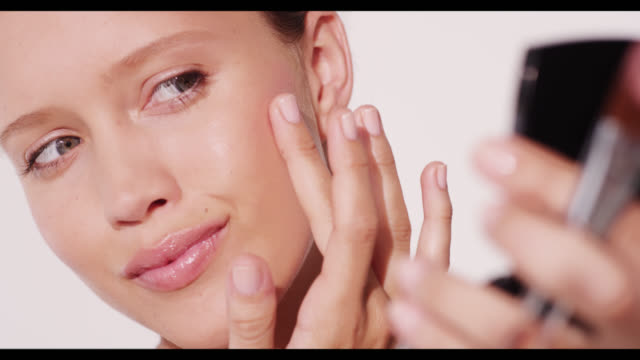 A woman rubs blusher in on her cheek with her finger