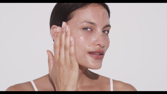 Woman rubs exfoliater into cheek with one hand