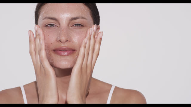 woman rubs exfoliater into cheeks with both hands - scrubbing stock videos & royalty-free footage