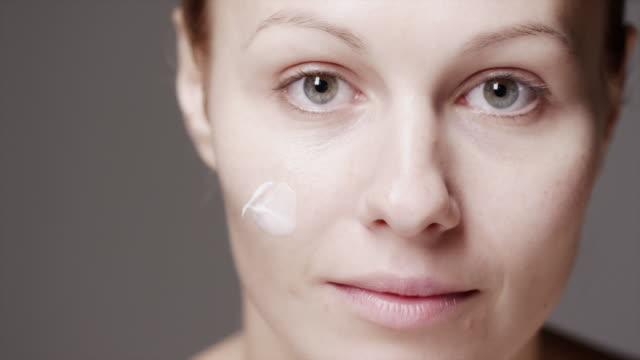 A woman rubs facial cream onto her cheek with her fingertips.