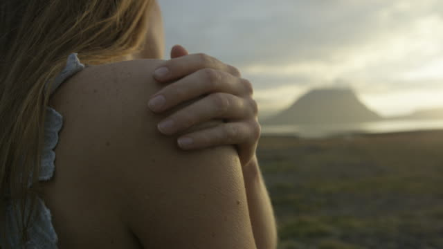 woman rubs hand down arm to warm herself - schöne natur stock-videos und b-roll-filmmaterial