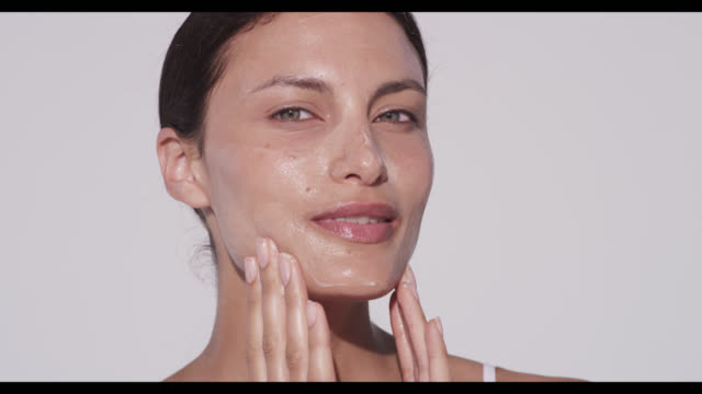 woman rubs in cleanser on face with both hands - facial mask beauty product stock videos and b-roll footage