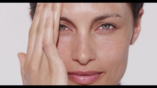 Woman rubs in cleanser on face with both hands
