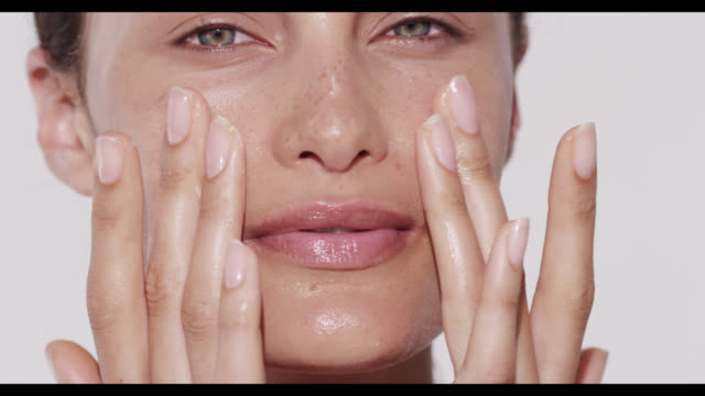 woman rubs in cleanser on face with both hands - viso video stock e b–roll