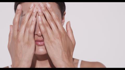 woman rubs in moisturiser into forehead with both hands - kroppsvård bildbanksvideor och videomaterial från bakom kulisserna