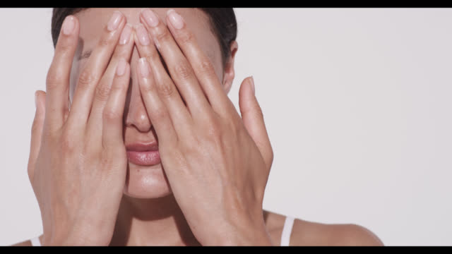 woman rubs in moisturiser into forehead with both hands - strofinare toccare video stock e b–roll