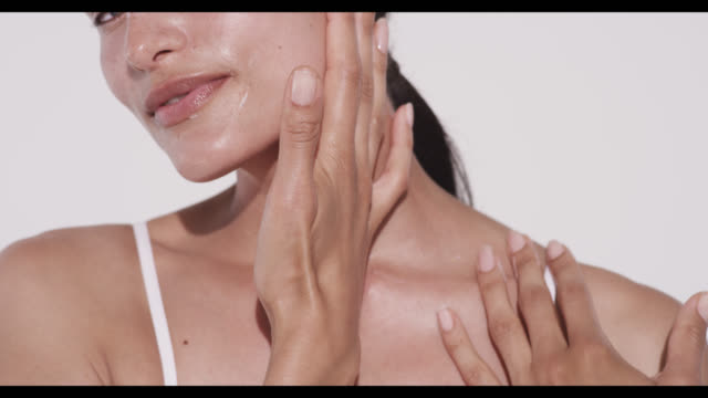 vidéos et rushes de woman rubs in moisturiser on cheek and neck with hand - beauty
