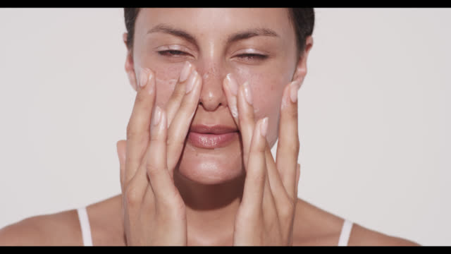 Woman rubs in moisturiser on cheeks with hands