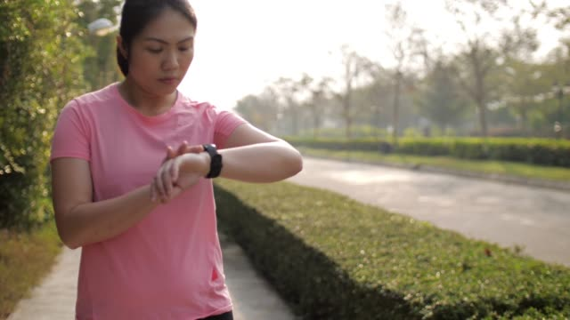 woman runner monitoring performance on smartwatch after running , slow motion - interval start stock videos & royalty-free footage