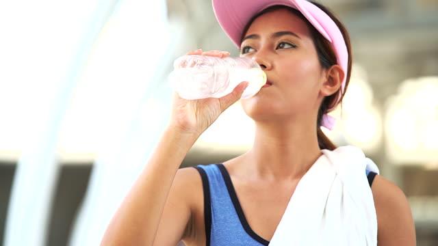 Vrouw loper buiten het joggen in de ochtend met stedelijke scène in de achtergrond. Het drinkwater van de jonge vrouw voor haar verfrissing tijdens het joggen.