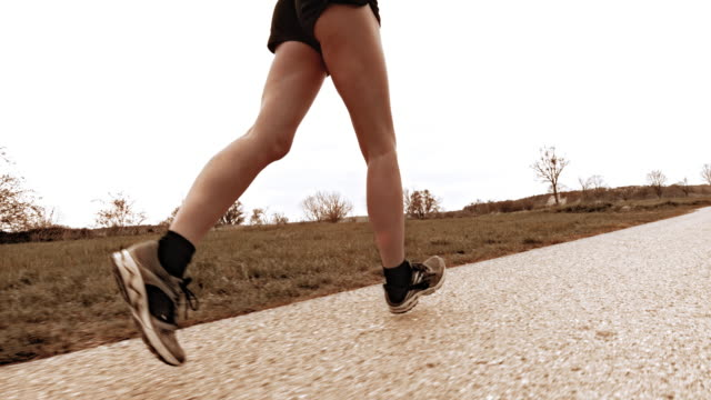 slo mo ts woman runner running along countryside road - running shorts stock videos and b-roll footage