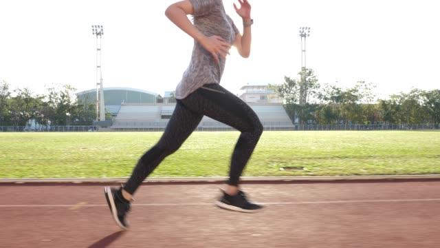 kvinna löpare körs i morgon med solljus - sedd från sidan bildbanksvideor och videomaterial från bakom kulisserna