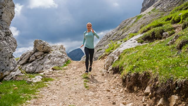 Woman runner running off road on mountain paths