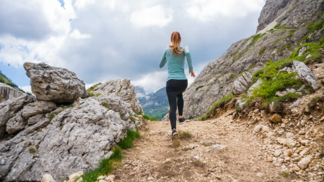 Woman runner running over rocky trails in mountain terrain