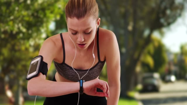 Woman runner using smartwatch fitness tracker while running in suburban park