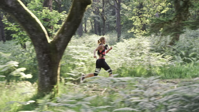 SLO MO DS Woman running a forest trail marathon