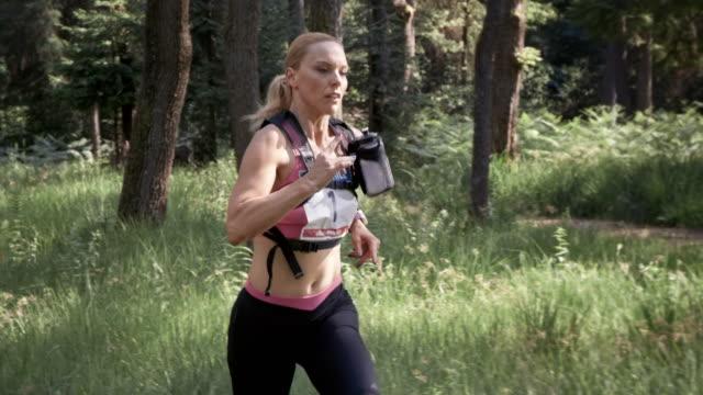 SLO MO DS 女性がマラソンの森の木に囲まれて