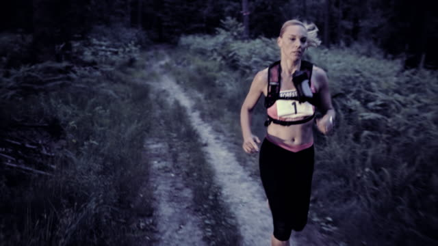 slo mo ds woman running a trail marathon at sunset - blonde hair stock videos & royalty-free footage