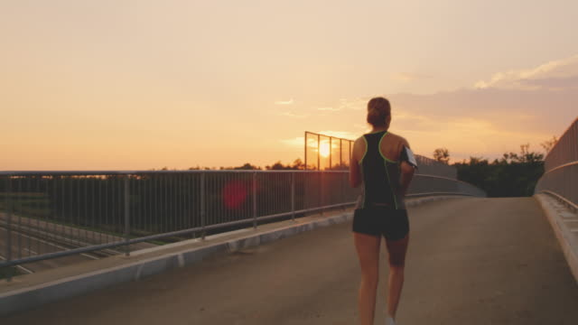 slo mo woman running across a bridge at sunset - top garment stock videos & royalty-free footage