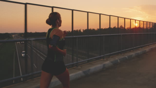 slo mo woman running across a bridge over a highway at sunset - vest stock videos & royalty-free footage
