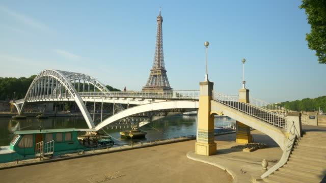 a woman running across a bridge with the eiffel tower. - slow motion - エッフェル塔点の映像素材/bロール