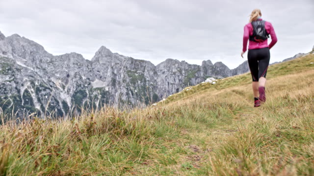 ld woman running across a grassy mountain ridge in the high mountain range - pedal pushers stock videos & royalty-free footage