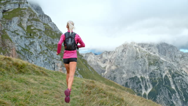 slo mo woman running across a meadow high in the mountains - footpath stock videos & royalty-free footage