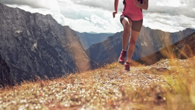 slo mo ld woman running across a sunny meadow high in the mountains - slovenia meadow stock videos & royalty-free footage