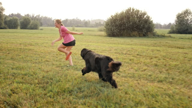 SLO MO Woman running across meadow with her dog