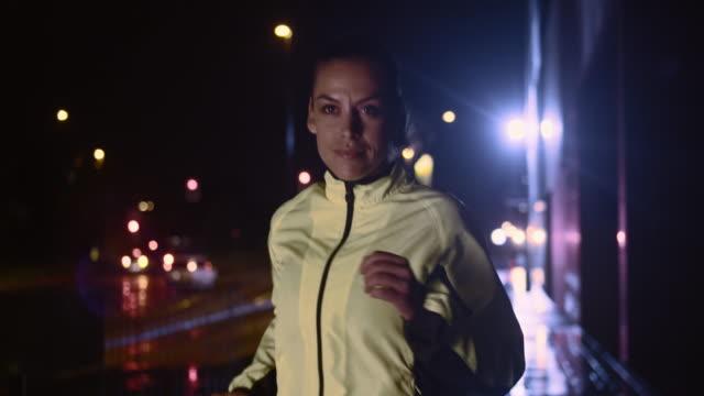 SLO MO Woman running along a city street at night