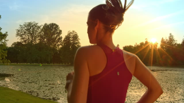 slo mo ts woman running along a lake at sunset - vest stock videos and b-roll footage