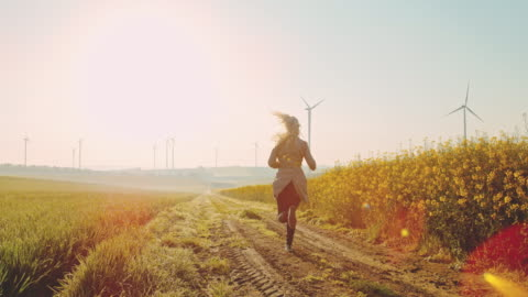 super slo mo - time warp effect woman running along field of canola with wind turbines in the distance - wind power stock videos & royalty-free footage
