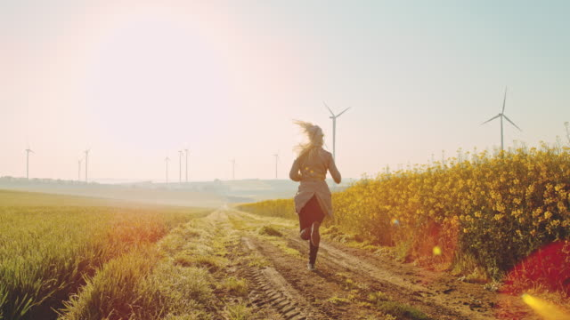 super slo mo - time warp effect woman running along field of canola with wind turbines in the distance - mill stock videos & royalty-free footage
