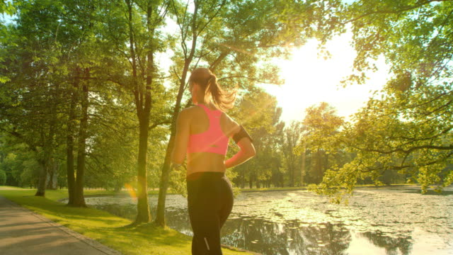 slo mo ts woman running along lake in sunshine - jogging stock videos & royalty-free footage