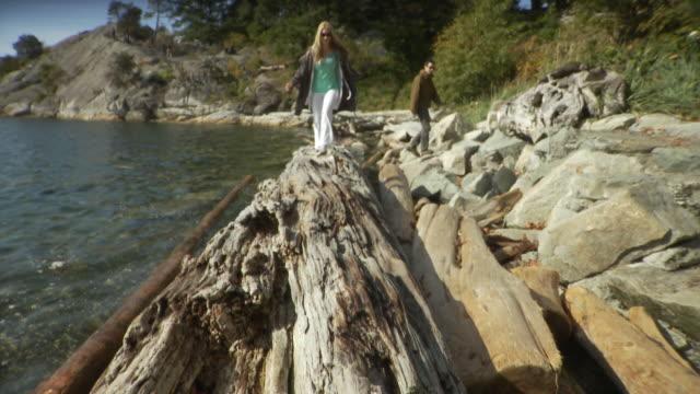 WS TU Woman running along log at Horseshoe Bay, man in background / Vancouver, British Columbia, Canada
