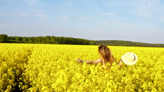 slo mo woman running among blooming canola - sun hat stock videos & royalty-free footage