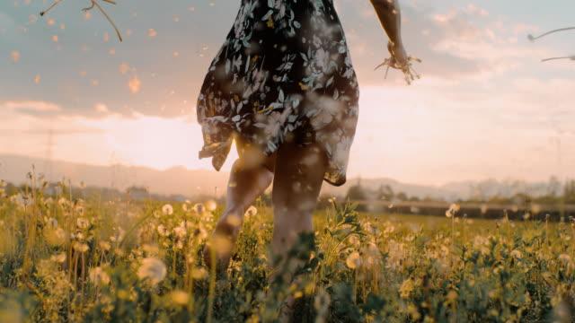 タンポポの間を走るslo mo女性 - 裸足点の映像素材/bロール