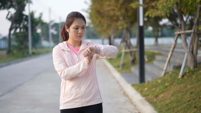woman running and checking smartwatch for monitoring her running performance - interval start stock videos & royalty-free footage
