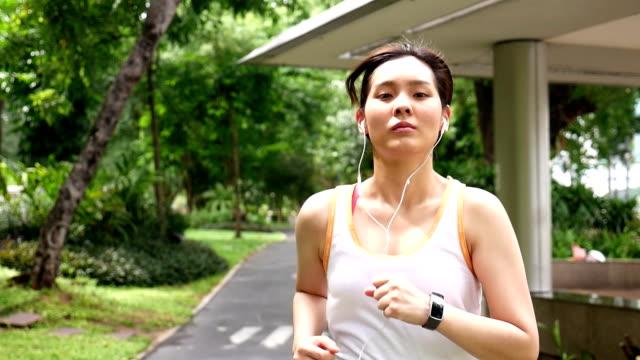 stockvideo's en b-roll-footage met slo mo ts vrouw rennen en luisteren in het park met oortelefoon - mid volwassen vrouw