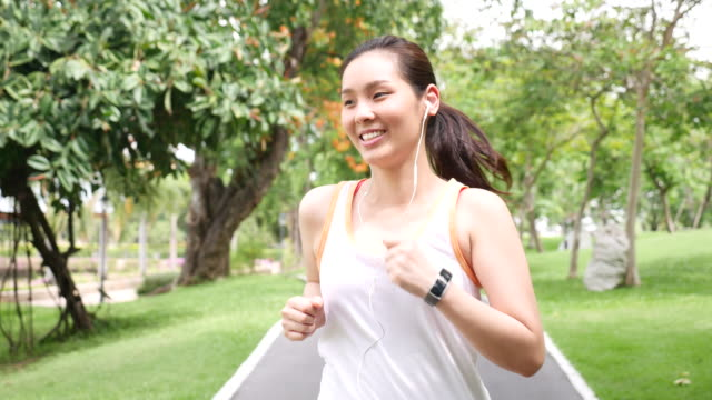 Woman running and Listening to music in city park with Smart watch and earphone