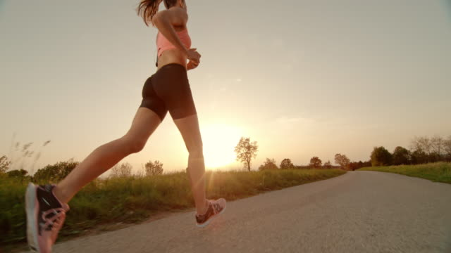 SLO MO TS TU Woman running as sun is setting