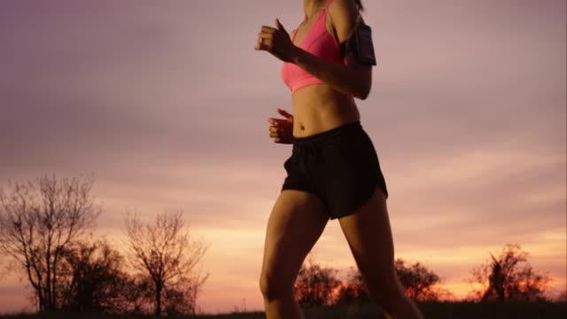 SLO MO TS Woman running as the sun is setting