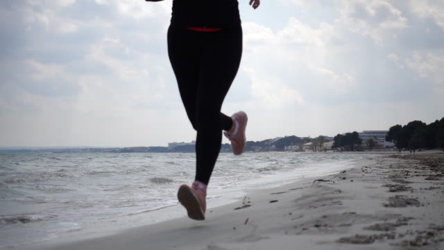 Woman running at beach.