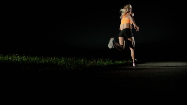 SLO MO PAN Woman running at night