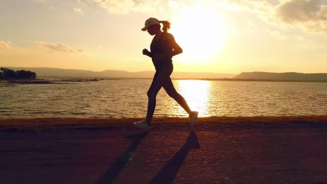 vidéos et rushes de femme qui court au coucher du soleil - jogging