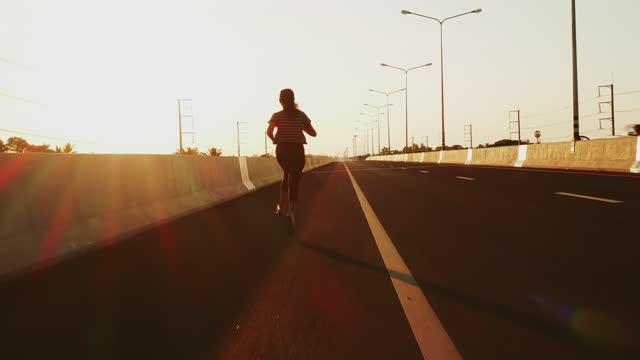 日没時に走るslo mo女性 - strength点の映像素材/bロール