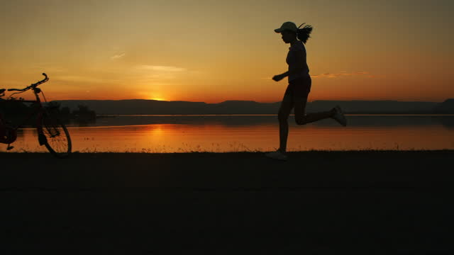 slo mo woman running at sunset - in silhouette stock videos & royalty-free footage